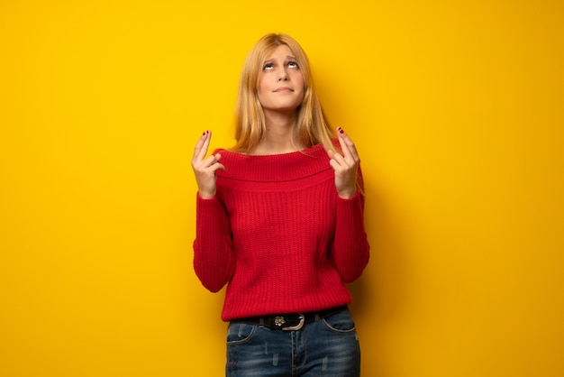 Blonde woman over yellow wall with fingers crossing and wishing the best