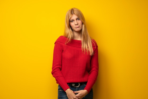 Blonde woman over yellow wall with sad and depressed expression