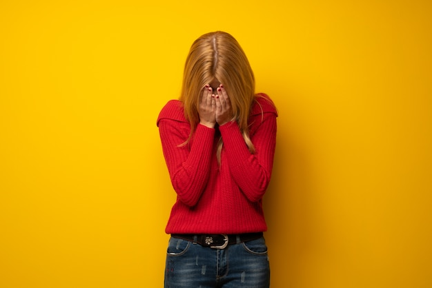 Blonde woman over yellow wall with tired and sick expression