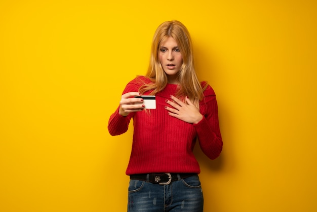 Blonde woman over yellow wall with troubled holding broken smartphone