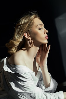 Светловолосые женщины с ювелирными серьгами в ушах в лучах вечернего солнца. красота лица длинные волосы чистая гладкая кожа, натуральная косметика макияж