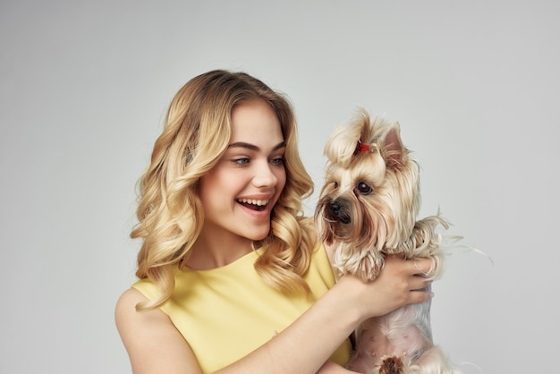 Blonde in a yellow dress fun a small dog isolated background