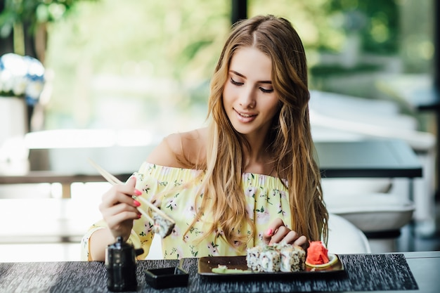 Blonde, young beautiful blond woman, student eating sushi on the summer terrace in a japanese restaurant