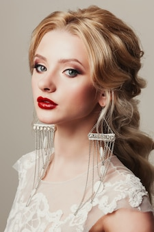 Blonde young bride with elegant earrings and red lipstick