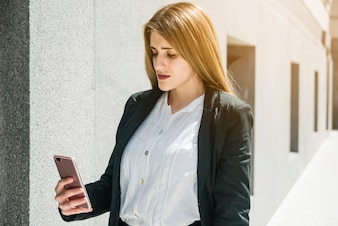 Blonde young businesswoman looking at smartphone