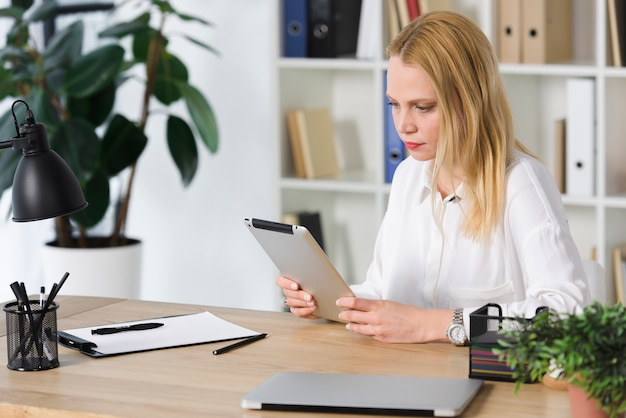 Blonde young businesswoman sitting at workplace looking at digital tablet in the office