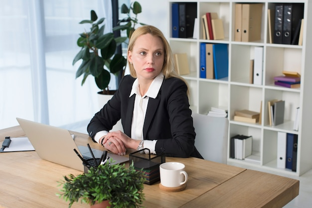 Blonde young businesswoman sitting at workplace in the office