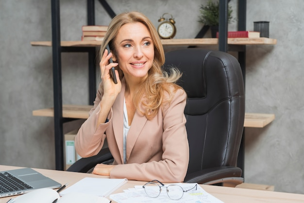Blonde young businesswoman talking on cell phone sitting on chair at office