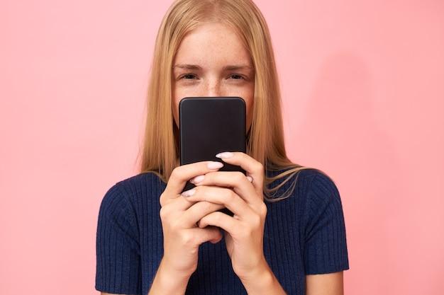 金髪の若い女性が目を細め、携帯を持って不審な表情をしている