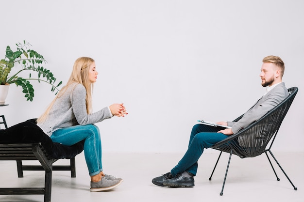 Blonde young female patient sitting on sofa at therapy session with male psychologist