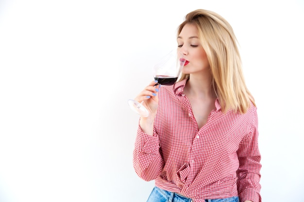 Blonde young girl in checkered shirt with red lipstick drinking wine from glass on white wall background, sommelier and expert concept
