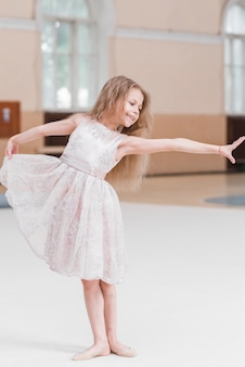 Blonde young girl dancing ballet on floor in dance studio