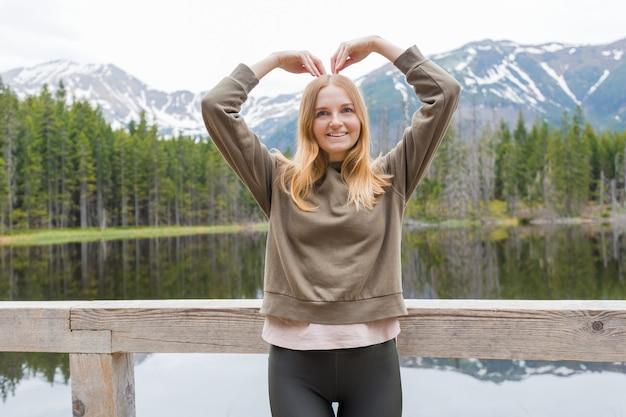 森の中の山の湖のそばでハートの形で手をつないでいる金髪の少女。旅行とアクティブライフのコンセプト。屋外
