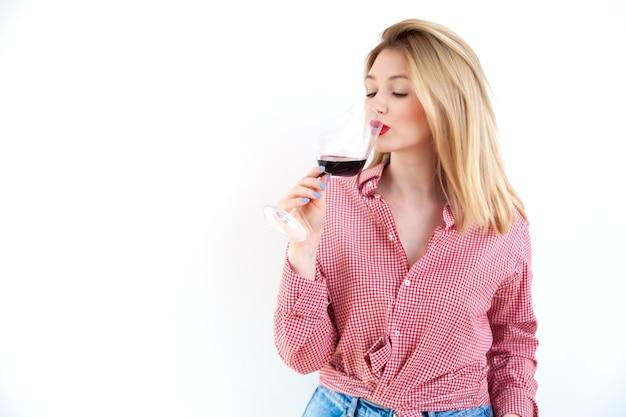 Молодая блондинка в клетчатой рубашке с красной помадой пьет вино из стекла на белом фоне стены, сомелье и экспертная концепция