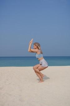 金髪の少女は晴れた日にビーチでガルーダサナ/イーグルポーズアーサナでヨガと瞑想を練習します。