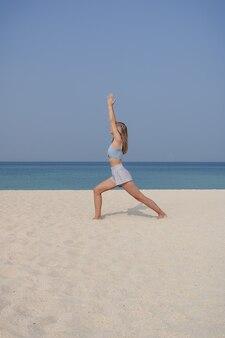 金髪の少女は、晴れた日にビーチで心配のポーズやvirabhadrasanaアーサナでヨガと瞑想を練習します。