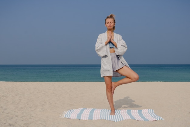 Blonde young girl practices yoga and meditation in the vrikshasana and tree pose asana on the beach on a sunny day.