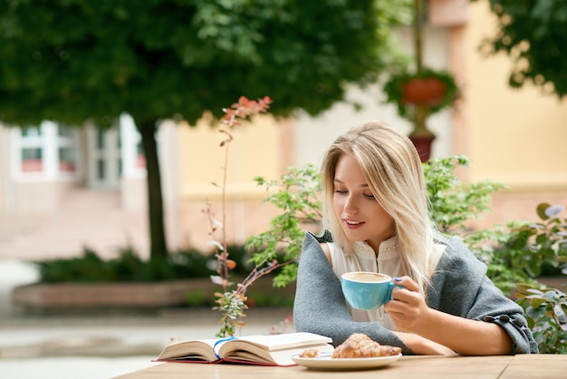 Blonde young girl reading interesting book while drinking coffee outdoors.