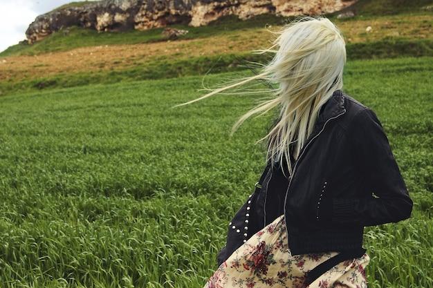 Молодая блондинка с модной одеждой на травянистом холме в ветреный день