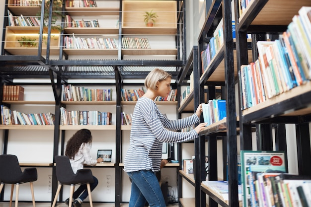 Giovane bella donna bionda in camicia a strisce e jeans alla ricerca di un libro sullo scaffale in biblioteca, preparandosi per gli esami in università