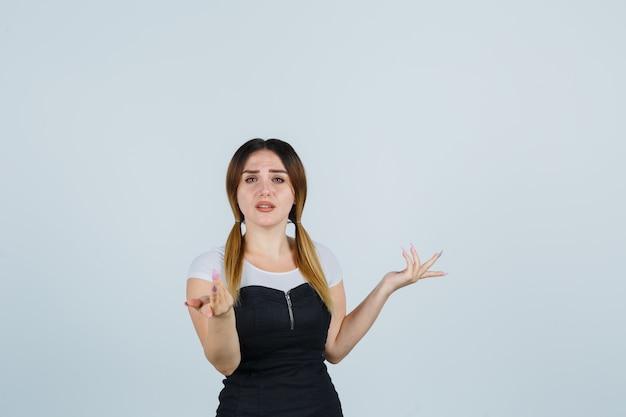 Giovane signora bionda in vestito che gesturing isolato