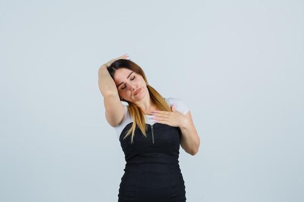 孤立した身振りでドレスの金髪の若い女性