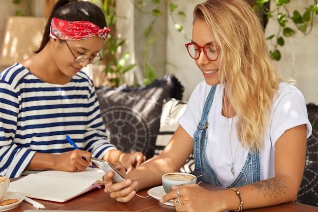 腕に入れ墨のある金髪の若い女性は、現代の携帯電話を保持します