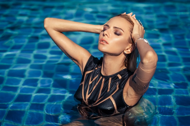 Blonde young model posing outdoor in the pool. demonstrate the black closed swimsuit from new summer collection. palm trees  . cool blue water. hands on the head, slim body.