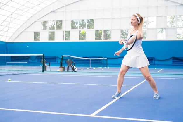 テニスをしている金髪の若いスポーツ選手