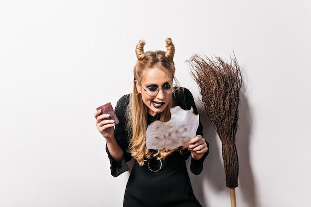 Blonde young witch in glasses reading spell. indoor portrait of evil wizard conjures in halloween.