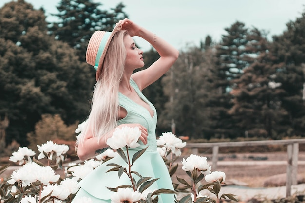 Blonde young woman in a birch dress in a floral garden, fashionable color correction photo