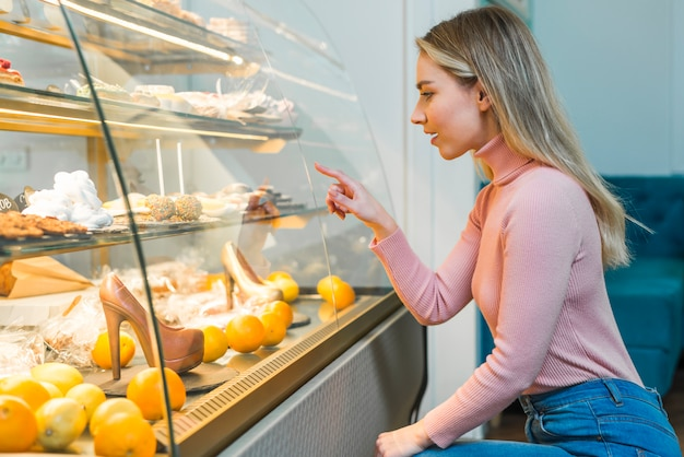 Blonde young woman choosing pastry from display cabinet in bakery