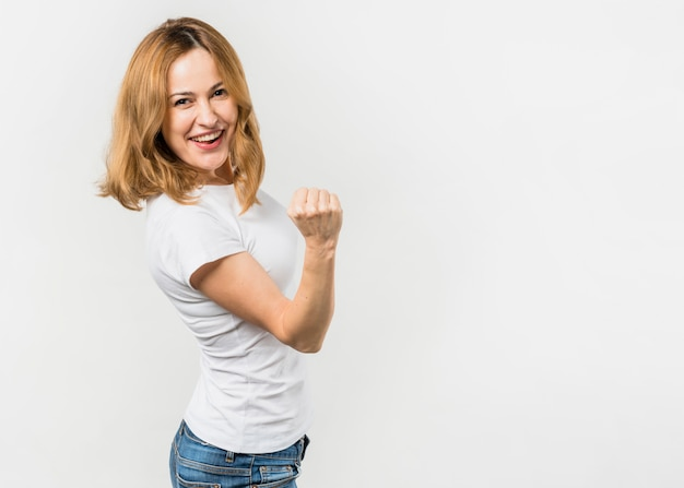 Blonde young woman clenching her fist standing against white background