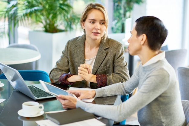 Blonde young woman discussing project with boss Premium Photo