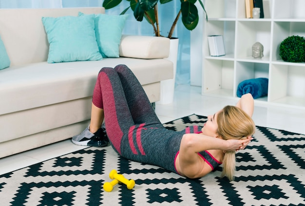Blonde young woman doing exercise on carpet in the living room