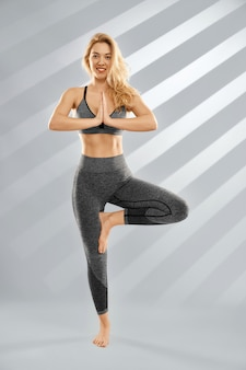 Blonde young woman doing yoga in trendy sportswear