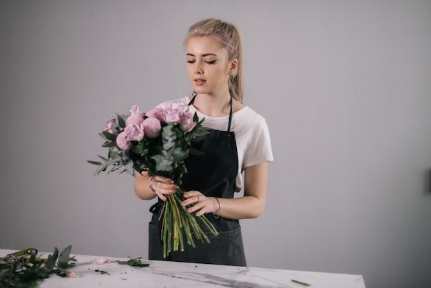 테이블에 꽃다발을 들고 앞치마를 입은 금발의 젊은 여성 꽃집