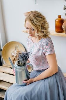 植栽バルコニーインテリアで花を保持している金髪の若い女性。健康的なライフスタイル、美容、エコ