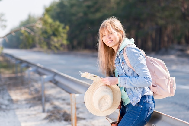 Blonde young woman holding hat and map standing near the road with her backpack looking at camera