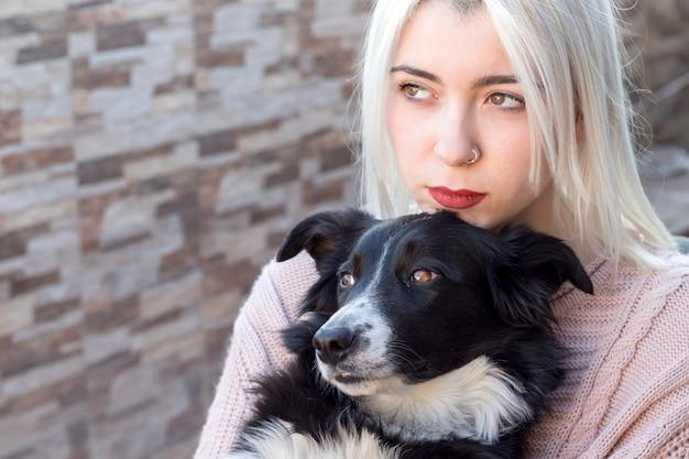 Блондинка молодая женщина обнимает свою собаку, сидя на открытом воздухе на террасе