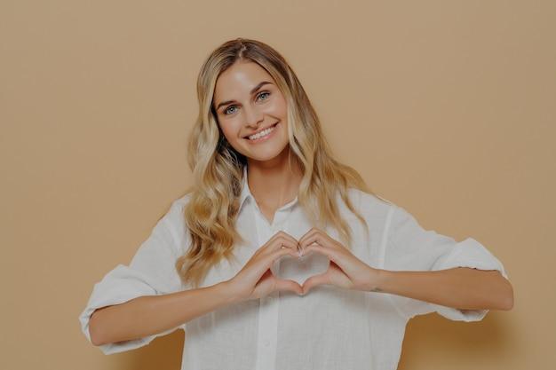 Блондинка молодая женщина в белой рубашке делает форму сердца руками, показывая свою любовь и восхищение кем-то, стоя изолированно перед оранжевым фоном. концепция признательности