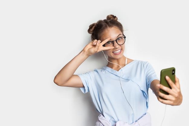 금발의 젊은 여자가 미소하고 여유 공간이있는 흰색 스튜디오 벽에 안경과 헤드폰을 착용하는 동안 셀카를 만들고 있습니다.