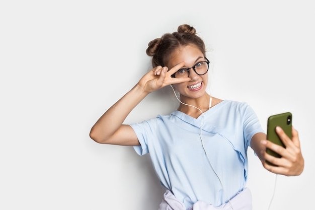 Blonde young woman is smiling and making a selfie while wear glasses and headphones on a white studio wall with free space
