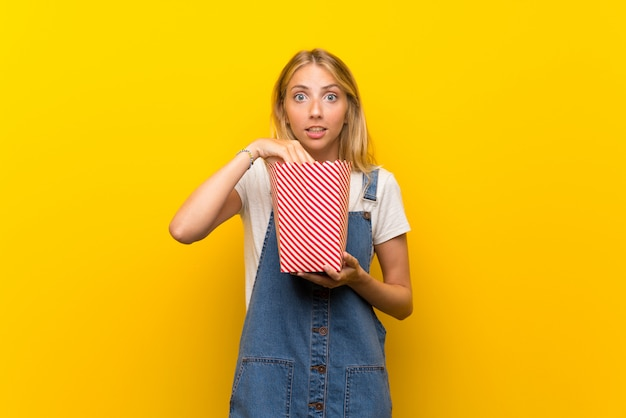 Blonde young woman over isolated yellow wall eating popcorns