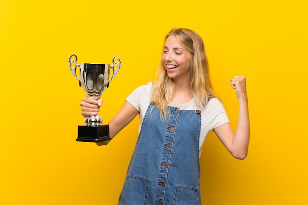 Blonde young woman over isolated yellow wall holding a trophy