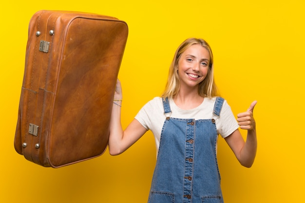 Blonde young woman over isolated yellow wall holding a vintage briefcase
