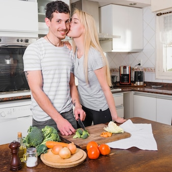 Blonde young woman kissing her husband cutting vegetable in the kitchen