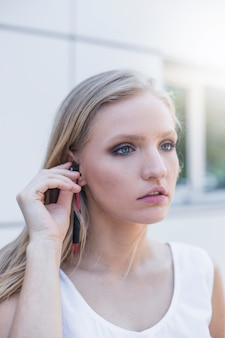 Blonde young woman listening music on earphone