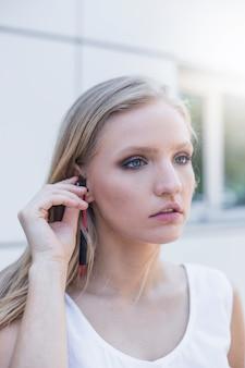 イヤホンでブロンドの若い女性が音楽を聴く