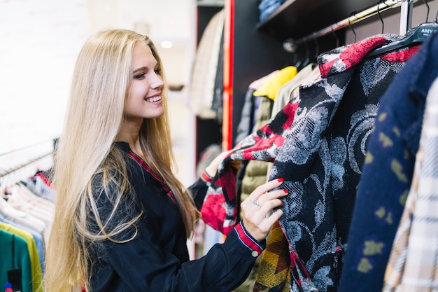 Blonde young woman looking at jackets in the rack